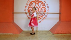 Little girl dances at stage, holding skirt of folk sarafan Stock Footage