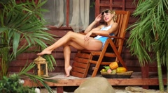 Woman sits on chaise lounge near bungalow, taking sunbathes. Stock Footage