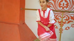 Smiling girl performs on stage holding skirt of sarafan. Stock Footage