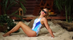Young woman sits on sandy beach near bungalow, taking sunbathes Stock Footage