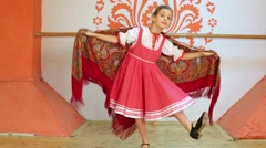 Smiling girl in red folk costume dances and spins with shawl Stock Footage
