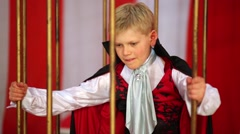 Little boy in suit and red cloak is pulled out from golden cells. Stock Footage