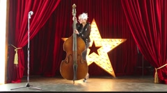 Woman plays contrabass and dances on stage at music hall. Stock Footage