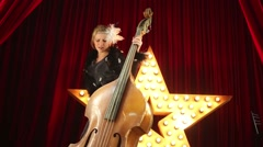 Woman plays old damaged contrabass and dances on stage. Stock Footage
