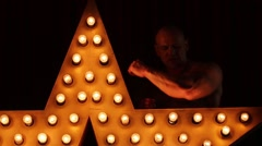 Strong bodybuilder stands leaning his arms on star with lights. Stock Footage