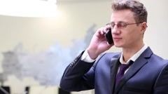 Businessman in glasses talks on cell phone at conference room. Stock Footage