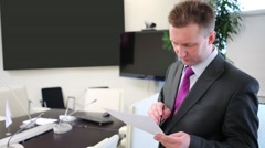 Businessman stands and scrutinizes document making marks. - stock footage
