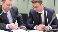 Two businessmen sit at table, scrutinizing and discussing document. - stock footage