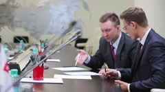 Two businessmen sit, scrutinizing and making marks to document. - stock footage