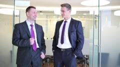 Two businessmen stand near open door to meeting room Stock Footage