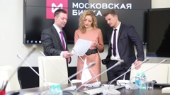 Business group of two men and one woman stands in conference hall Arkistovideo
