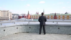 Man in business suit stands on open roof terrace raising his arms Stock Footage