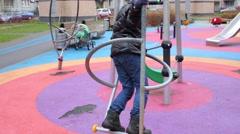 Boy spins on a swing at modern children playground. Stock Footage