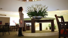 Woman stands in hall near to big flowerpot, then leaves room. Stock Footage