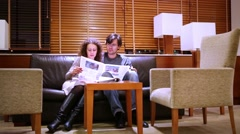 Man and woman sit together on sofa in hall, talk Stock Footage