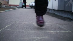 Legs of girl playing hopscotch on asphalt at spring day Stock Footage