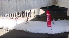 Skiers on track under bridge at Race of Skiers Champions Stock Footage