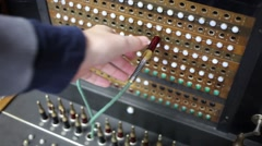 Hand touches wires, board for connection of telephone subscribers - stock footage