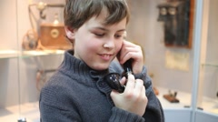 Boy talks on the phone in Museum of phone Stock Footage