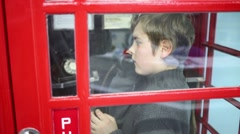 Boy talks on phone in red telephone box in Museum of phone Stock Footage