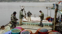 Professional Fishermans repair fishnet, fishing net together on landed boat Stock Footage