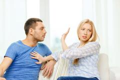Unhappy couple having argument at home Stock Photos