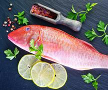 Raw fish with spice on black board Stock Photos