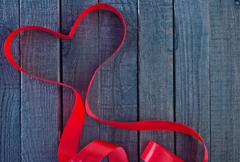 Red ribbon on the wooden table Stock Photos