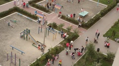 Children play in the playground in the garden game court swing teeter-totter Stock Footage
