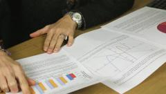 attractive female hispanic business executive looking at graphs and statistics - stock footage