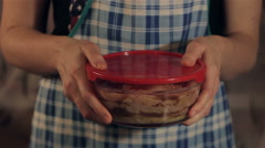 Girl in apron holding food container with chicken marinade Stock Footage