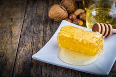 Honey dipper and honeycomb, nuts of various kinds Stock Photos
