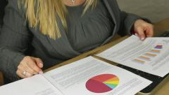 Attractive blonde female business executive looking at graphs and statistics Stock Footage