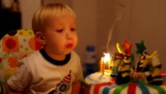 Adorable three year old boy celebrating his birthday and blowing candles Stock Footage