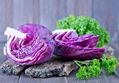 Blue cabbage on board and on a table Stock Photos