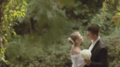 Groom and bride in a beautiful dress kissing in the park Stock Footage