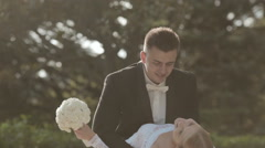 Groom tips bride and kisses her in park Stock Footage