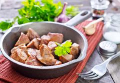 Fried meat in pan and on a table Stock Photos