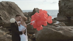 Enamoured newlyweds stand with balloons in the form of heart in the rocks by the Stock Footage