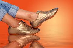 Stock Photo of sport golden footwear and womens foots on water