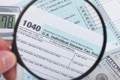 Stock Photo of United States of America Tax Form 1040 with magnifying glass