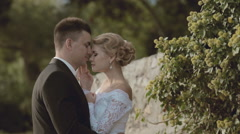 Bride and groom standing near a stone wall in the park Stock Footage