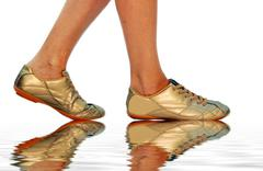 Stock Photo of sport golden footwear and womens legs
