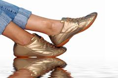 Stock Photo of sport golden footwear and womens foots