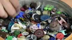 Dish of various colorful buttons and needlewoman finger choose Stock Footage