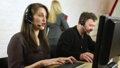 Friendly customer service call centre staff chatting to customers on headsets  - stock footage