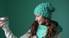 Beautiful girl in a knitted hat holding a mug Stock Footage