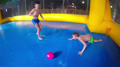 Tow teen fun boys play in football on water surface. Water falls and splashes Stock Footage