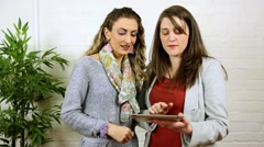 happy smiling chatting hispanic and white women using ipad tablet app - stock footage