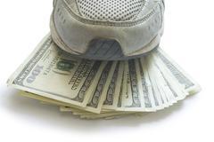 Money under running shoe - stock photo
